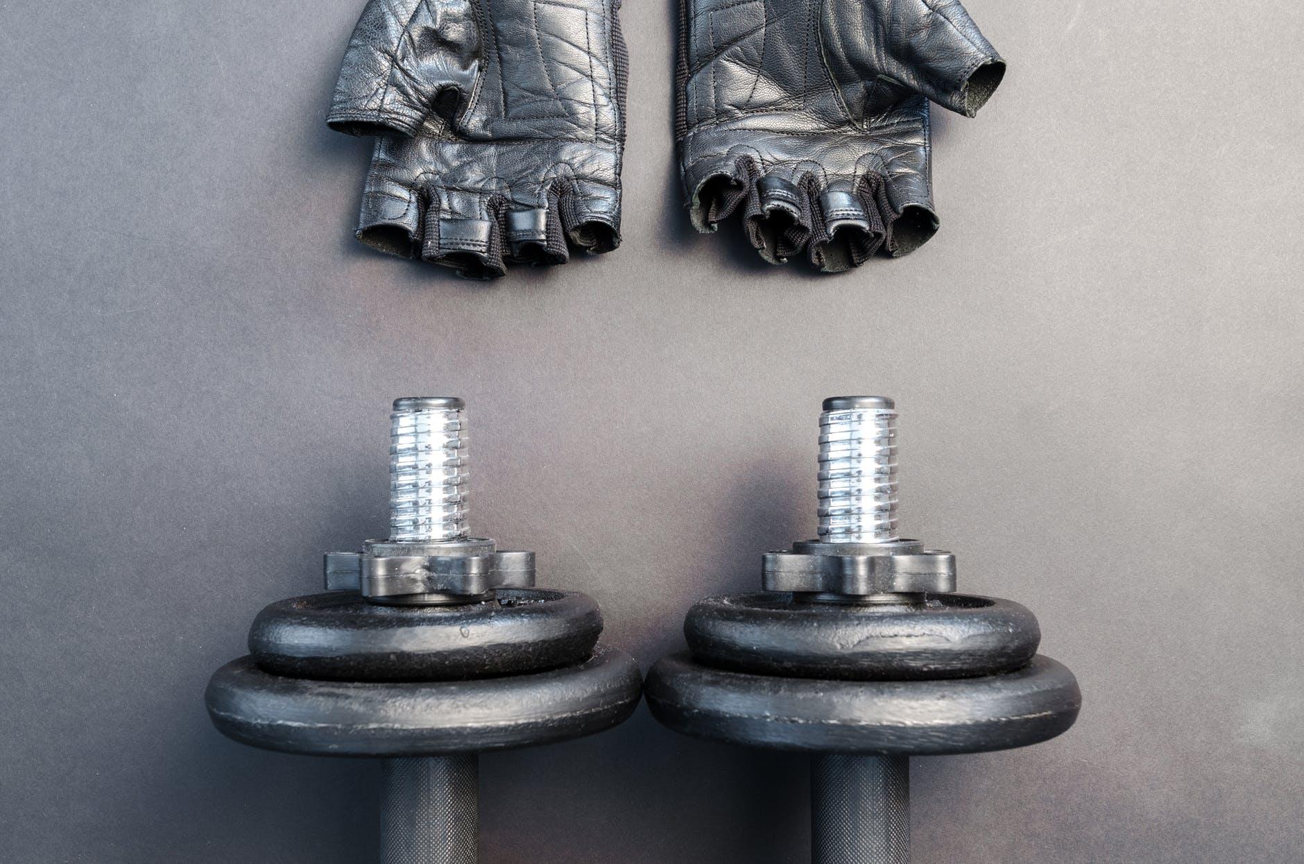 pair of fingerless gloves and adjustable dumbbells