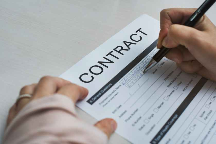 person signing contract paper