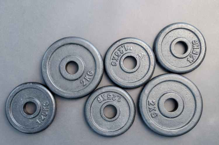 six assorted weight plates on top of gray surface