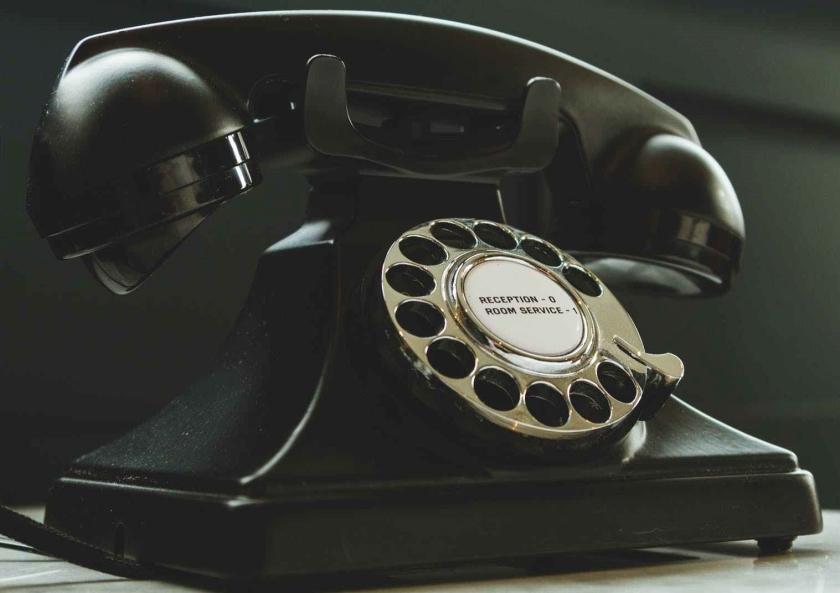 black rotary telephone on white surface